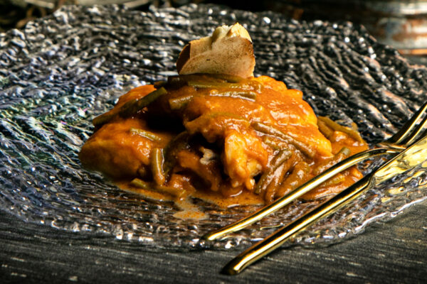 Merluza en salsa de pimientos y ajetes tiernos